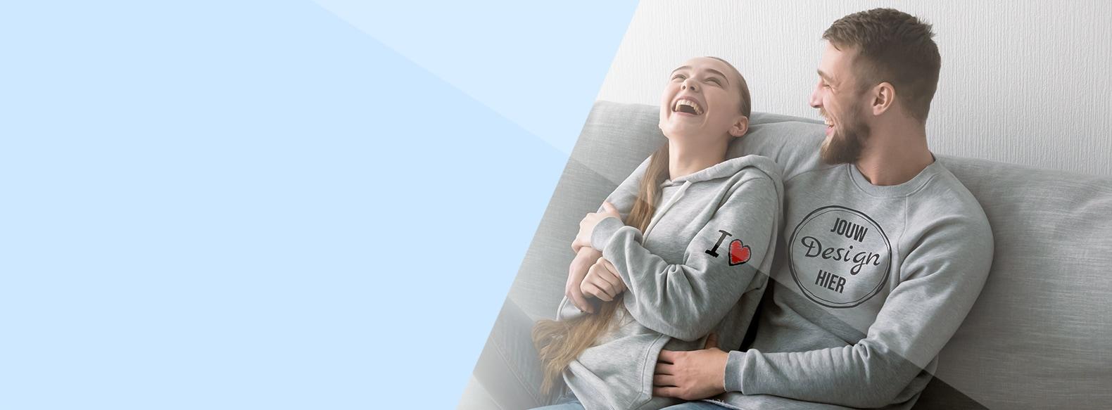 Koppel in hoodies met eigen ontwerp zitten in de sofa